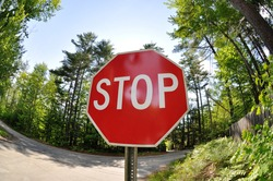 fisheye stop sign in summer on a rural road with forest in the background