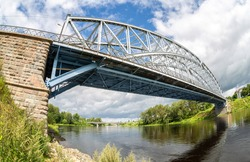 Fisheye view on the first in Russia steel arch bridge across the Msta river in summer day. Built in 1905. Borovichi, Russia