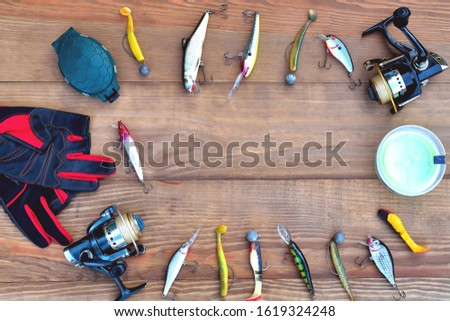 fishing accessories fishing rod, reel with fishing line, silicone baits and lures, spinning gloves and accessory box on a wooden background, close-up, copy space flat lay