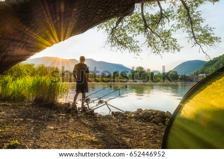 Fishing adventures, carp fishing. Angler, at sunset, is fishing with carpfishing technique. Camping on the shore of the lake. Fisherman in backlight