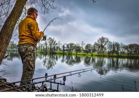 Fishing adventures, carp fishing. Angler is fishing with carp-fishing technique.