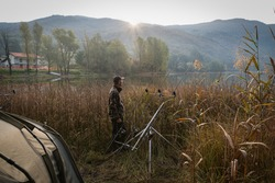 Fishing adventures, carp fishing in autumn. Camping on the lake at sunrise; sun rising from the mountain and man with camouflage fleece on the shore, hidden behind the reeds