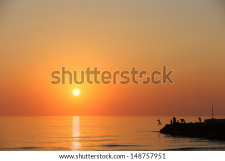 stock-photo-fishing-and-jumping-into-the-water-at-dawn-on-the-mediterranean-148757951.jpg
