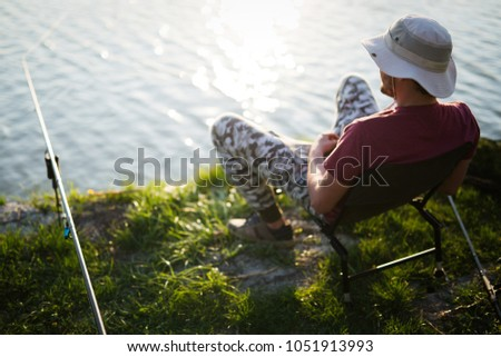 Fishing as recreation and sports displayed by fisherman at lake #1051913993