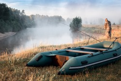 Fishing at dawn on a small river with fog over the water. On the shore is an inflatable rubber boat for fishing, fishing rods, a man fishing.
