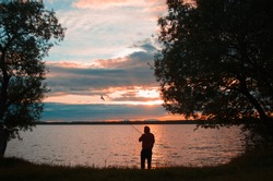 Fishing at sunset on the lake. Fisherman throws a fishing rod, back view. Sunset landscape on the lake and a flying seagull.