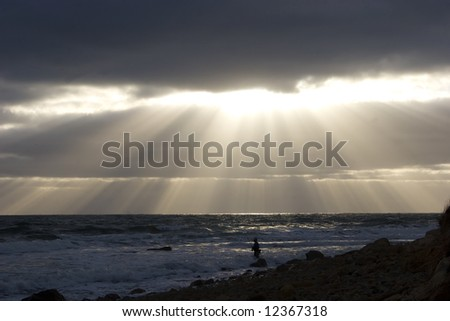 Fishing at the break of day at Montauk Point, Long Island. Sunrays finding a opening though the clouds.