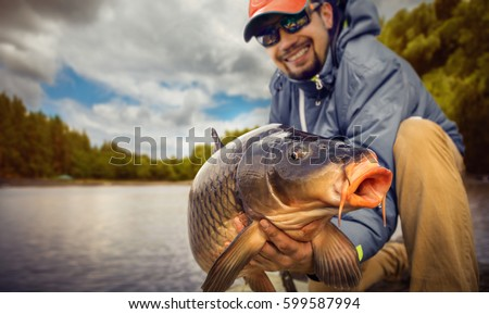 Fishing backgrounds. Young man hold big carp in his hands.
