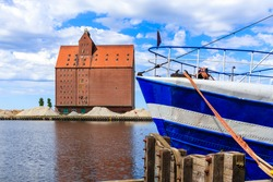 Fishing boat anchoring in Darlowo port with historical building in background, Baltic Sea coast, Poland
