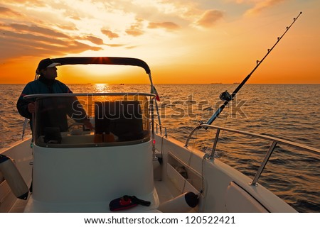 Fishing boat and fisherman in ocean at dawn