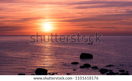 Fishing boat and fishermen on water at a sunset. Tranquil sea with no waves