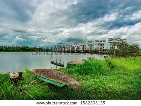 Fishing boat and water barrier and river with color of cloud sky storm in rain season #1562303155