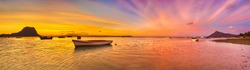 Fishing boat at sunset time. Le Morne Brabant on background. Mauritius. Panorama