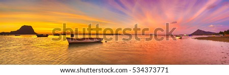 Fishing boat at sunset time. Le Morne Brabant on background. Mauritius. Panorama