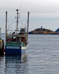 Fishing boat at the dock with a lighthouse in the background.