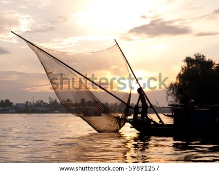 Fishing boat catching fish with fishnet at dusk on the Mekong river. Can Tho, Vietnam