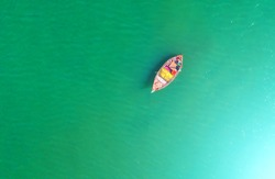 Fishing boat floating in the sea. The beautiful bright blue water in a clear day.Aerial view.Top view.