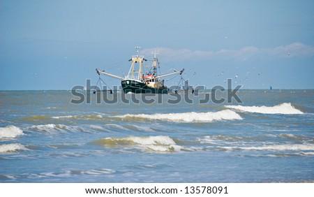 Fishing boat followed by seagulls.