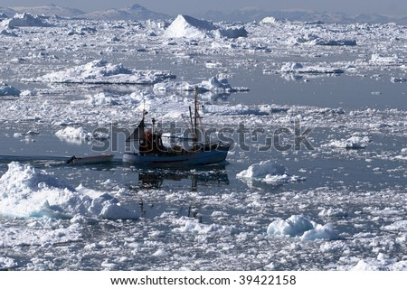 Fishing boat going through the icy waters of Ilulissat, Greenland