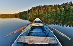 fishing boat in a calm lake water/old wooden fishing boat/ wooden fishing boat in a still lake water