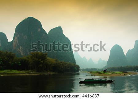 Fishing boat in calm waters  amongst grotesque mountain formations near Guilin China