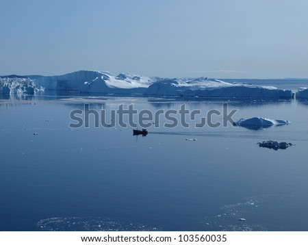 Fishing boat  in front of the icebergs at the mouth of Ilulissat Icefjord.