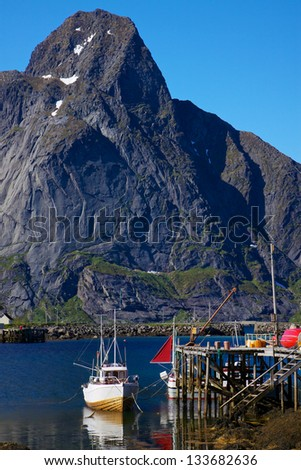 Fishing boat in town of Reine on Lofoten islands with high peak above fjord