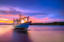Fishing boat in tropical beach with beautiful sunset time.
