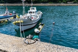 Fishing boat is fixed to the bollard by a rope. Fishing port of Saga prefecture, JAPAN.