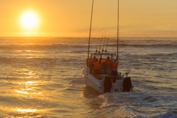 Fishing boat launching at sunrise with fishing rods and outboard motors.