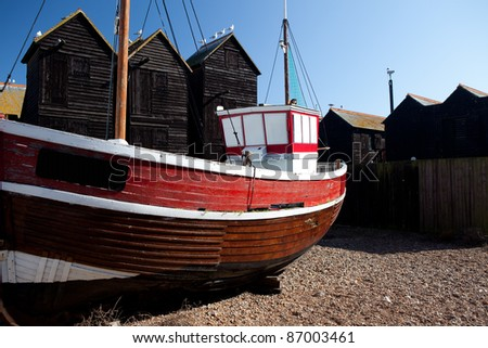 Fishing boat moored on coast next to fishing huts in village of  Hastings in England. Red Ship and black architecture
