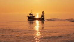 Fishing boat on a calm sea in early morning sunlight. Aldeburgh, Suffolk. UK