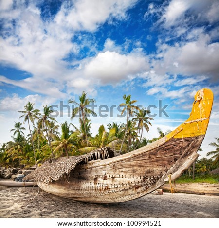 Fishing boat on the beach at dramatic cloudy sky at palm trees background