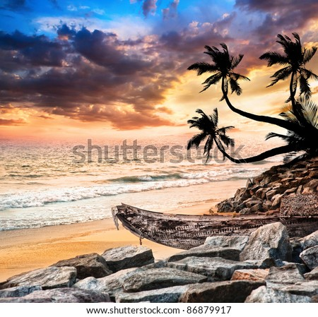 Fishing boat on the beach near the ocean at dramatic sunset sky and palm trees in silhouette nearby