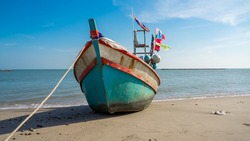 fishing boat on the beach with blue sky background in Thailand