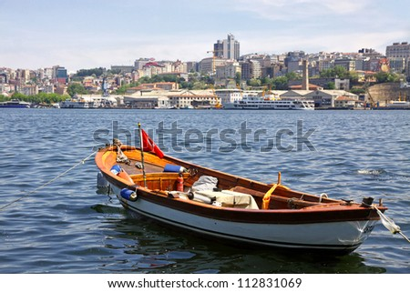 Fishing boat on the Golden Horn Gulf with Istanbul downtown, Turkey
