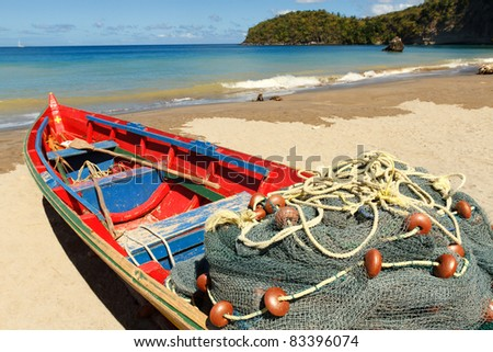 Fishing boat on the light sands of a Caribbean beach with turquoise sea in the background
