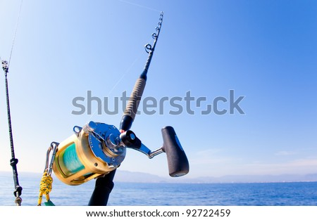 fishing boat trolling in ocean with golden reel rod #92722459