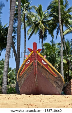 Fishing boat under the palm trees on the shore