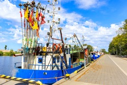 Fishing boats anchoring in Darlowo port with historical building in background, Baltic Sea coast, Poland