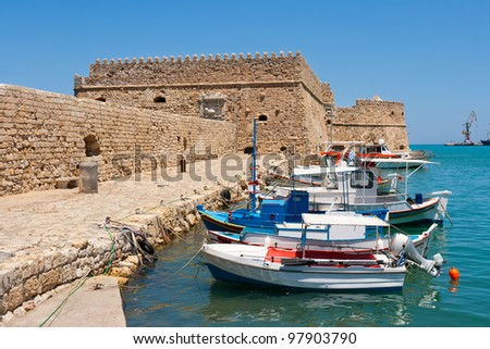 Fishing boats and Venetian Fortress in Heraklion harbor. Crete, Greece