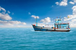 Fishing boats are overwhelmingly in the midst of the sea on a beautiful blue sky.