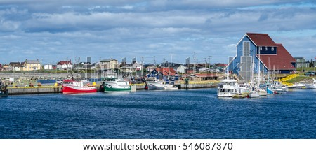 Fishing boats at docks in the villages' harbours in Bonavista, Newfoundland, Canada.   Newfoundland fishing villages see boats at rest for the day on calm coastal water.