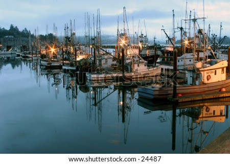 fishing boats dock during sunset with reflections in the water along the oregon coast
