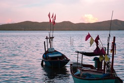 Fishing boats during the peak of color during the evening sunset at Kung Wiman beach in Chanthaburi, Thailand