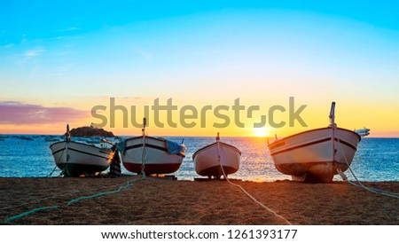 Fishing boats in the Mediterranean Sea on sunrise background