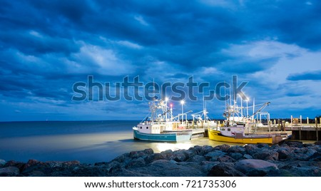 Fishing boats moored in Alma, Bay of Fundy, on the New Brunswick Atlantic coastline in Canada. Blue hour shot with dramatic clouds.