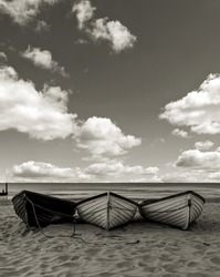 Fishing boats on a beach black and white, with cloudy sky