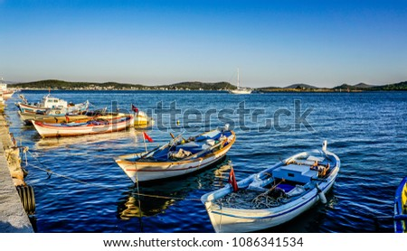 Fishing boats on the coast or seaside. Anchored boats waiting in the seaport or harbor in the Cunda Island on Aegean Sea, Turkey.
