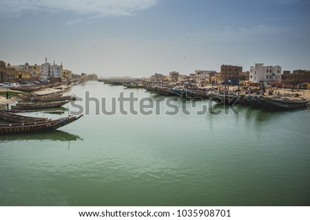Fishing boats parked on the shore in Sant Lois, a city in northern Senegal. Colorful boats, called pirogues are waiting in a canal.